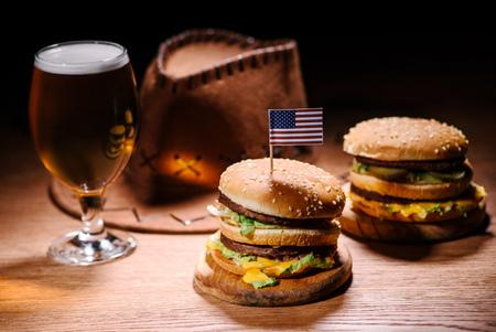 Sabrosas hamburguesas en la mesa de madera con sombrero de vaquero americano y vaso de cerveza fría