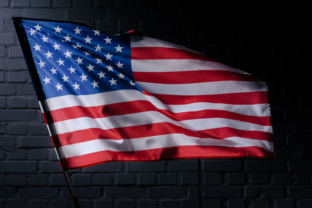 waving usa flag in front of black brick wall, Independence Day concept