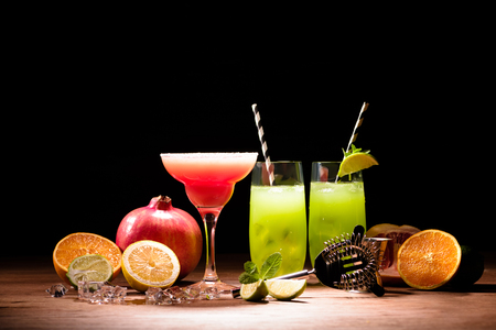 alcohol cocktails with lime and pomegranate on table