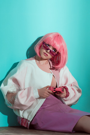 fashionable pretty girl in pink wig sitting on floor and playing with pink joystick