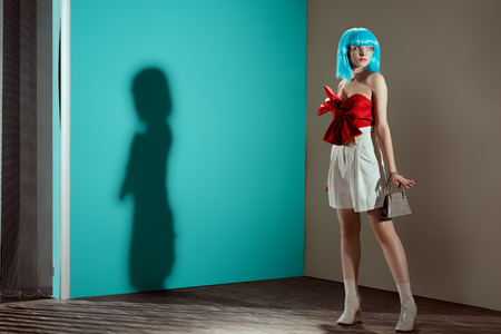 full length view of beautiful stylish girl in blue wig posing and looking away in studio