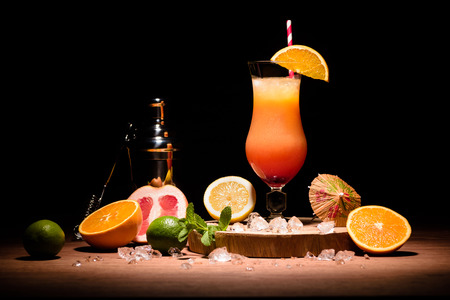 alcohol cocktail with orange juice on wooden board with fruits on table