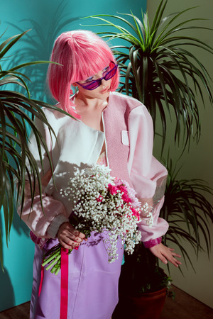 high angle view of fashionable girl in pink wig holding bouquet of flowers and looking away