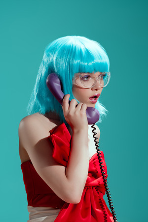shocked stylish girl in blue wig talking by telephone and looking away isolated on blue Reklamní fotografie
