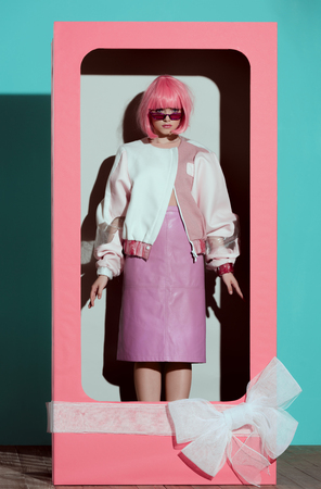 beautiful fashionable girl in pink wig standing in decorative box with bow and looking at camera