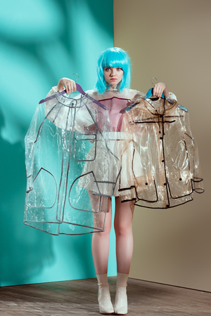 beautiful girl in blue wig holding hangers with transparent raincoats and looking at camera