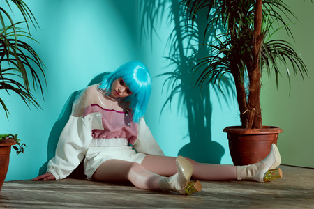 stylish girl in blue wig pretending to be a doll and sitting on floor between potted plants
