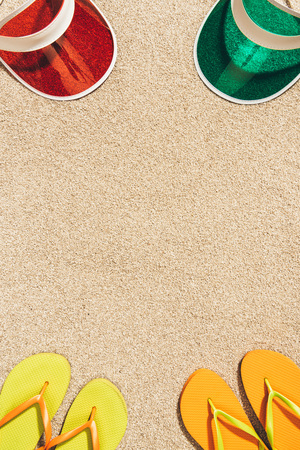 top view of arranged colorful caps and flip flops on sand