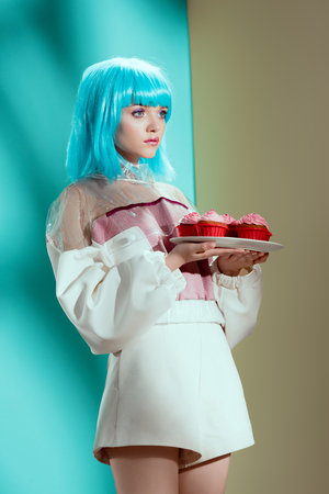 stylish girl in blue wig holding cupcakes and looking away in studio