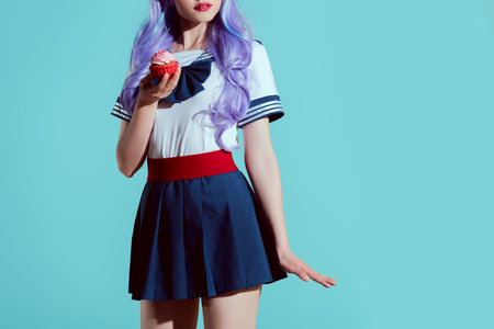 cropped shot of girl in anime clothing holding delicious cupcake isolated on blue Stock Photo