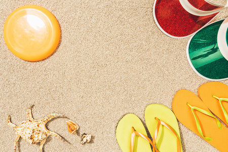 flat lay with flying disk, colorful caps, flip flops and seashells on sand 版權商用圖片