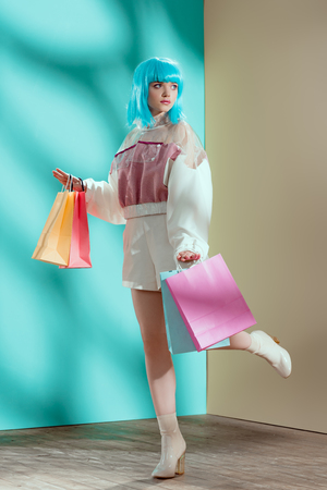 full length view of beautiful stylish young female model in blue wig holding shopping bags and looking away 版權商用圖片