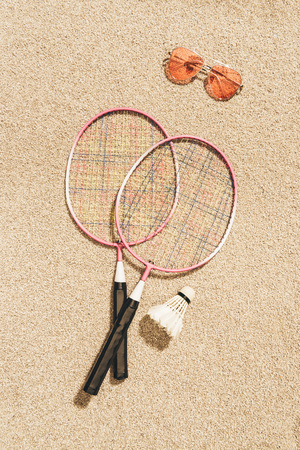 top view of arranged badminton equipment and sunglasses on sand