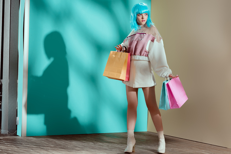 full length view of stylish pretty young female model in blue wig holding paper bags and looking away