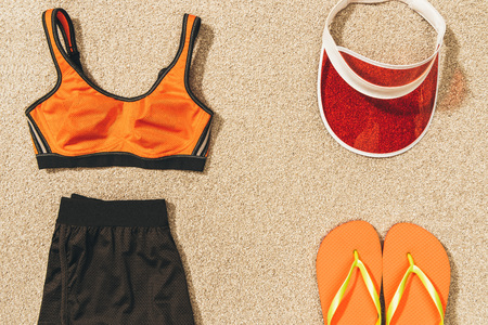top view of cap, flip flops and feminine sportswear arranged on sand