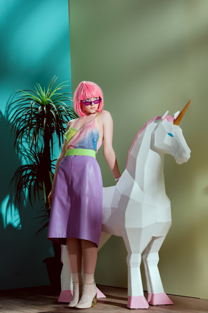 fashionable beautiful girl in pink wig leaning at unicorn