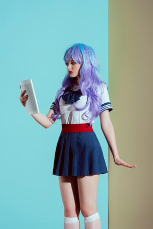 young woman in bright wig using digital tablet in studio