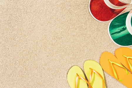flat lay with colorful flip flops and caps arranged on sand Imagens