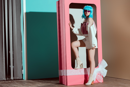 fashionable young woman in blue wig posing in decorative pink box with bow 版權商用圖片