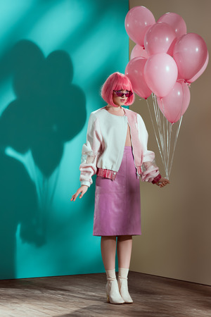 beautiful fashionable young female model holding pink balloons