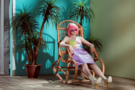 full length view of attractive stylish female model in pink wig sitting in rocking chair