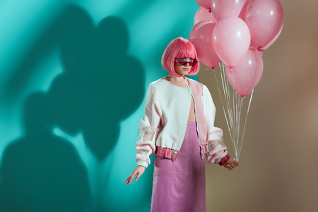 stylish pretty girl in bright wig holding pink balloons and looking away