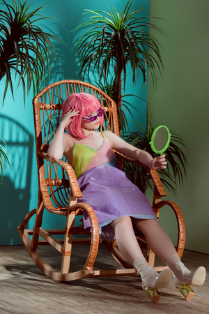 fashionable young female model in pink wig sitting in rocking chair and looking at mirror 版權商用圖片
