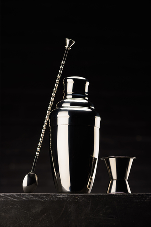 shaker for preparing alcohol cocktail on table isolated on black