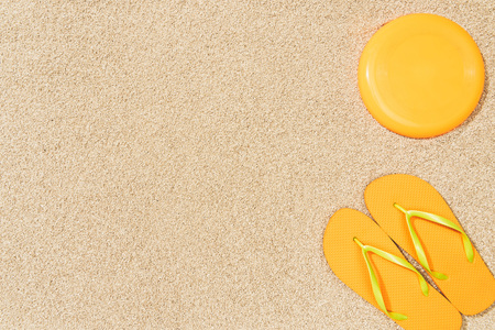 top view of yellow flip flops and frisbee on sand 版權商用圖片