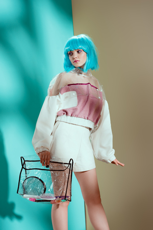 stylish girl in blue wig holding transparent cosmetic bag and looking away 版權商用圖片