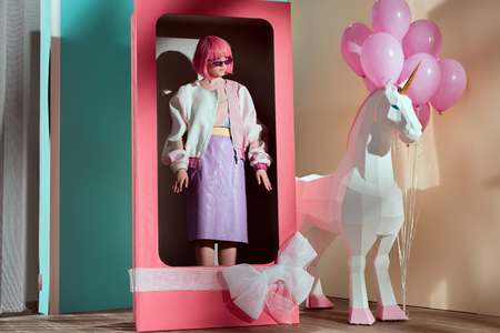 female model in pink wig standing in decorative box with bow 版權商用圖片