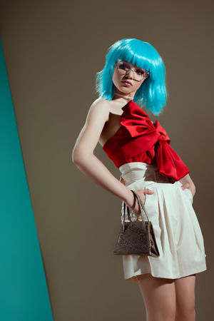 low angle view of beautiful female model in blue wig standing with hands on waist in studio