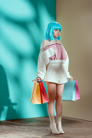 full length view of fashionable young female model in blue wig holding shopping bags and looking away
