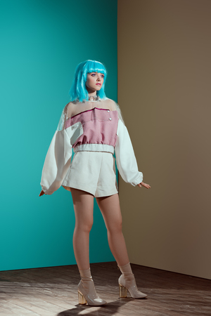 full length view of fashionable female model in blue wig posing and looking away in studio