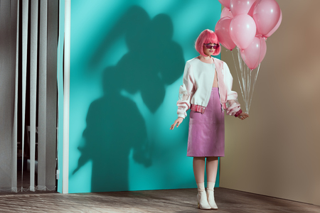 full length view of stylish pretty girl in bright wig holding pink balloons 版權商用圖片