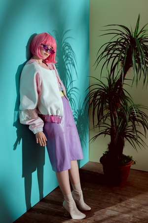 full length view of fashionable female model in pink wig leaning at wall and looking at camera