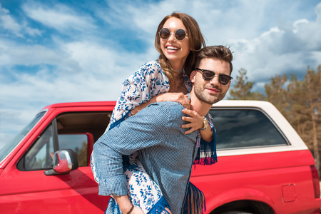 young smiling couple in sunglasses piggybacking near red car Foto de archivo