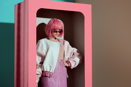 beautiful fashionable girl in pink wig posing with hand on waist in decorative box
