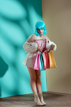 attractive stylish female model in blue wig holding shopping bags