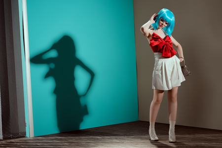 full length view of beautiful fashionable female model in blue wig posing and looking down