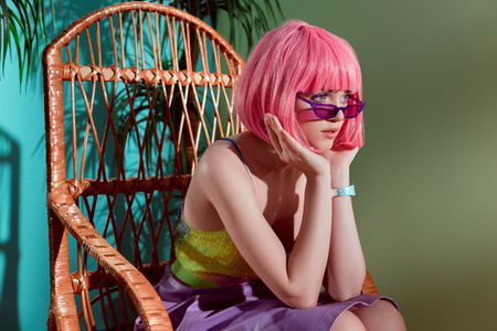 beautiful fashionable young female model in pink wig sitting in rocking chair and looking away 版權商用圖片
