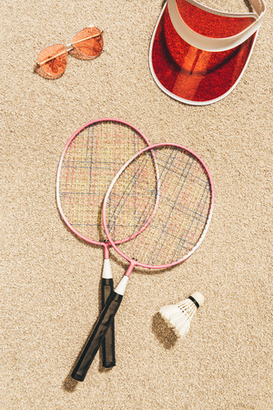 top view of badminton equipment, sunglasses and cap on sand Stock Photo