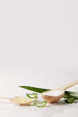 closeup view of aloe vera leaf and slices, two spoons with juice and salt on white surface Reklamní fotografie