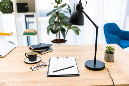 close up view of cup of coffee, eyeglasses, documents and lamp at workplace in office