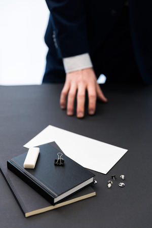 partial view of businessman in suit at workplace with notebooks, pins and blank paper