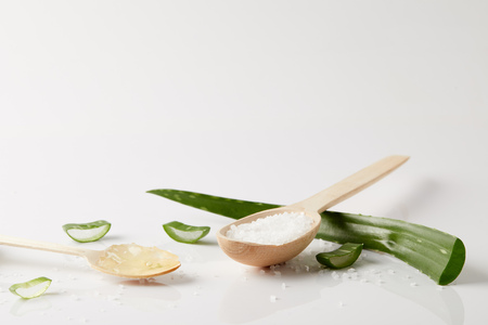 closeup view of two wooden spoons with aloe vera juice and salt, aloe vera leaf and slices on white surface Reklamní fotografie