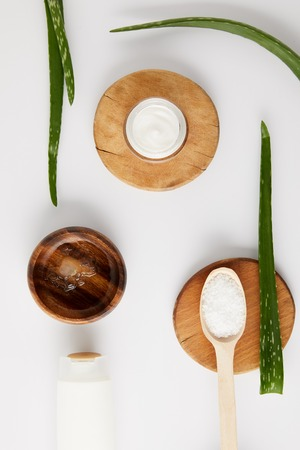top view of organic cream in container and spoon with salt on wooden slices, aloe vera leaves and wooden bowl with aloe vera juice 写真素材