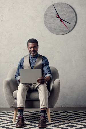 mature african american businessman with laptop sitting in armchair in office with clock on wall Stock Photo