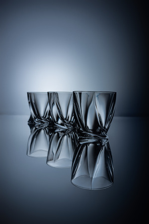 row of empty cognac glasses on grey with reflections