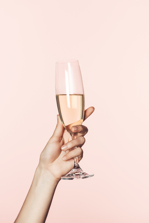 cropped shot of woman cheering by champagne glass isolated on pink background Banco de Imagens